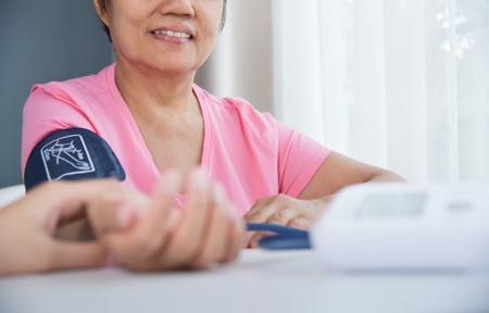 Foto de Asian Female doctor checking a senior woman patient pulse. Health care. Blood pressure. - Imagen libre de derechos