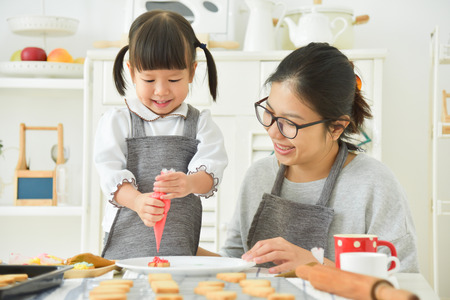 Photo pour Happy Asian Kid and young mother decorating cookies in the kitchen. - image libre de droit
