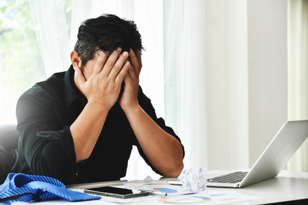 Photo for Stressed businessman is failing and serious in office. Bankrupt Asian Male is sitting with laptop computer and papers work at his workplace. Overtime, Overworked concepts. - Royalty Free Image