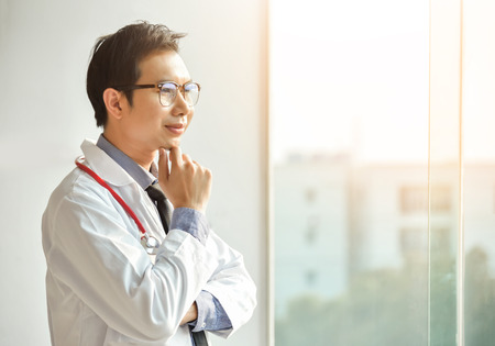 Foto de Portrait of Young Asian male Doctor is posing with arms crossed and looking through the window. copy space. Thinking. - Imagen libre de derechos
