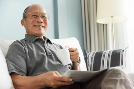 Photo for Happy Asian senior man smiling and drinking hot coffee while reading newspaper at his house. Relaxed, Free time, Smiling, Retirement. - Royalty Free Image