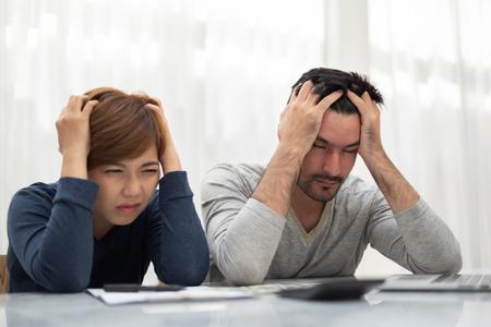 Foto de Stressed Young couple calculating their budget for new house. - Imagen libre de derechos
