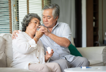 Foto de Asian Senior Woman taking medicines and drinking water while sitting on couch. Old man take care his wife while her illness at the house. - Imagen libre de derechos