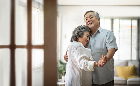 Foto de Cheerful Asian Senior couple dancing and smiling at home. Copy space. - Imagen libre de derechos