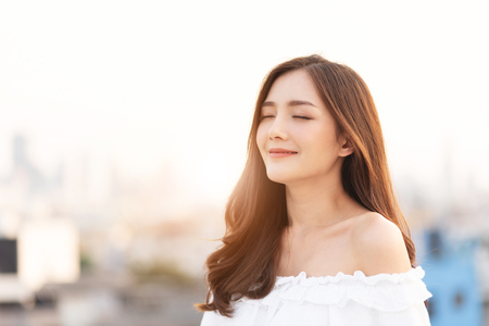 Photo for Beautiful Asian Woman is breathing fresh air. Smiling Female is standing on top of house roof over city background at outdoor. Relaxation, Eyes closed. - Royalty Free Image