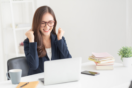 Foto de Excited Asian business woman after searching a job with a laptop at the office. Successful female wear glasses with victory gesture at the white room. Celebration. - Imagen libre de derechos