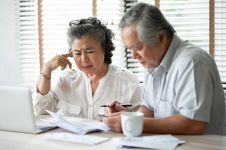 Foto de Serious Asian Senior Couple thinking about their Debts with laptop computer. Saving, Financials, monthly expense with Retirement. - Imagen libre de derechos