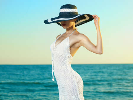 Foto de Photo of a beautiful young woman in a hat by the sea - Imagen libre de derechos