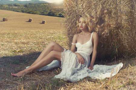 Photo pour Photo of sexy blonde in a field with haystacks - image libre de droit