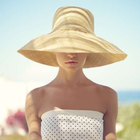 Photo pour Beautiful young lady in straw hat in the sunlight - image libre de droit
