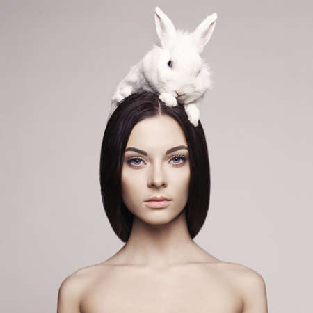 Photo for Studio fashion portrait of beautiful lady with white rabbit - Royalty Free Image
