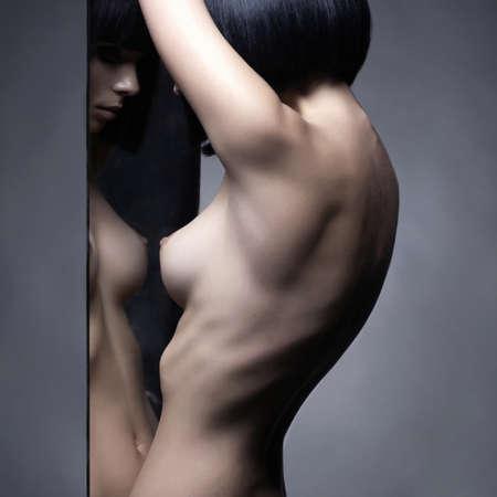 Photo pour Fashion studio portrait of nude elegant woman and mirrors on black background - image libre de droit