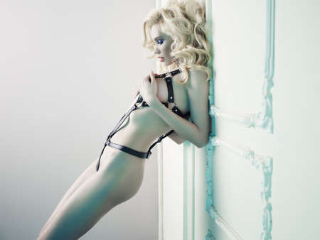 Foto de Fashion photo of nude elegant woman in provocative leather swordbelt in classical interior. Fetish lingerie - Imagen libre de derechos