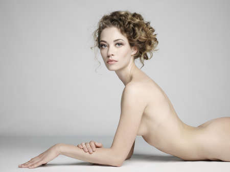 Photo pour nude sexy beautiful woman with long stylish hairstyle pose on white background in photostudio. Erotic portrait of elegant nude lady with perfect naked body. Sexual photography of young nude blonde. Sensual model with long hair sits in studio. Pretty strip - image libre de droit