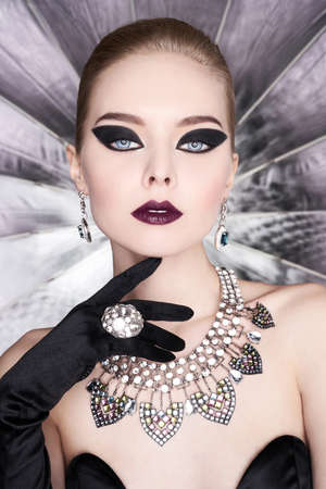 Photo pour Fashion studio photo of beautiful elegant woman with bright makeup and with set jewelry. Fashion arrow shape. Woman in necklace with ring and earrings. Glamorous Gatsby style - image libre de droit