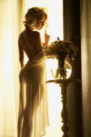 Foto de Lifestyle art photo of beautiful sensual blonde with flowers at the window. Home interior. Beautiful morning - Imagen libre de derechos
