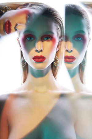Foto de Studio portrait of sexy lady with blonde hair. Beautiful girl with bright makeup and earrings.Portrait with mirrors. - Imagen libre de derechos