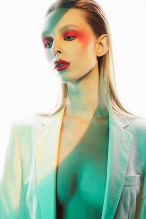Foto de Studio portrait of sexy lady with blonde hair. Woman posing in white jacket. Beautiful girl with bright makeup. - Imagen libre de derechos