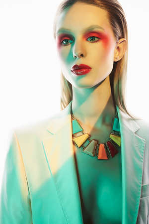Foto de Studio portrait of sexy lady with blonde hair. Woman posing in colorful neacklace and white jacket. Beautiful girl with bright makeup. - Imagen libre de derechos