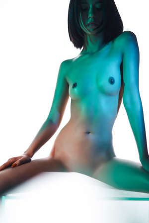 Foto de Naked body of young sexy woman with beautiful figure. art photosession with colorfull bright light on nude model. Erotic modern portraits of sensuality girl with perfect figure. white background. - Imagen libre de derechos