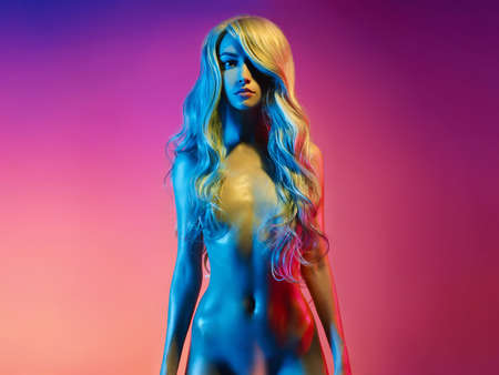 Photo for Nude beautiful blonde dancing in colorful light. Erotic portrait of sexy woman with long hairs. Sexual naked model pose on pink background. Perfect female body of elegant stripper. Pretty girl. - Royalty Free Image