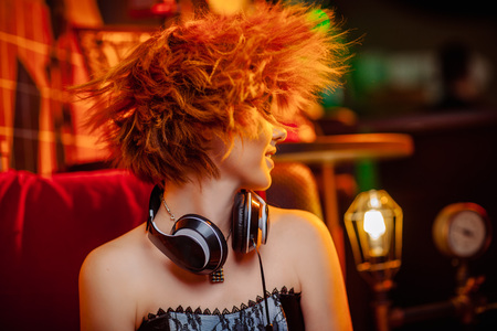 Photo pour Redhaired girl in headphones with unusual makeup at the disco - image libre de droit