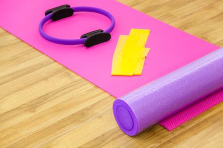 Foto de Roller, yoga mat, stability ring and yelow cloth on the parquet. Close-up shot. - Imagen libre de derechos