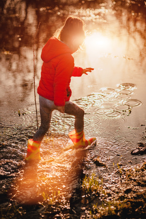 Photo for Side view of girl in jacket and gumboots walking happily in muddy puddle back lit with bright sunset light. - Royalty Free Image