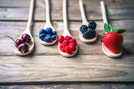 Photo pour Berries on wooden rustic background - image libre de droit