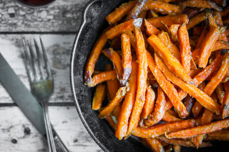 Photo for Sweet potato fries in cast iron skillet on wooden background - Royalty Free Image