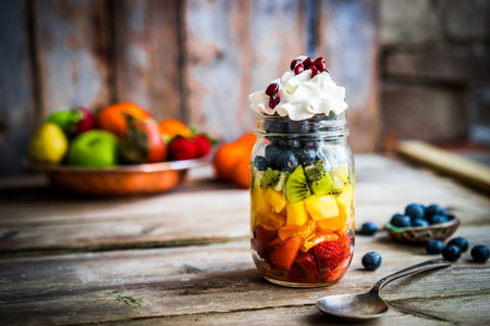 Photo for Colorful fruit salad in a jar on rustic wooden background - Royalty Free Image