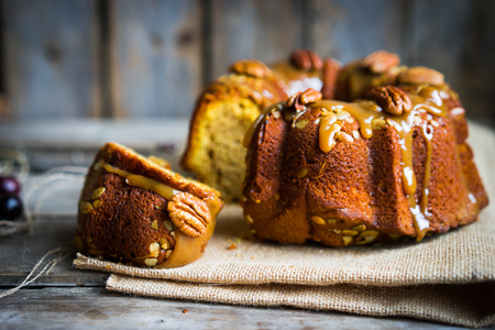 Foto de Homemade autumn cake with nuts and caramel on wooden background - Imagen libre de derechos