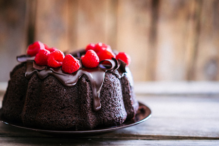 Photo for Chocolate cake with raspberries on rustic wooden background - Royalty Free Image
