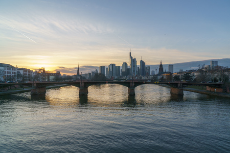 Foto de Stunning sunset view of the financial skyline in Frankfurt. Pictures were taken from the Floesserbruecke during blue hour in february. Thus the office rooms already have their lights on and having lots of light effects on the main river. - Imagen libre de derechos