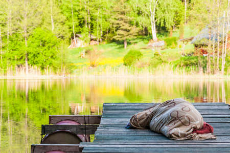 Photo for Amazing lake in the middle of emerald forest. Adult is sleeping on wooden pier covered with plaid. Waterscape dreaming in Lithuania. - Royalty Free Image
