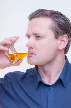 Photo for Portrait of young Caucasian Ethnicity man with blue shirt drinking whiskey brandy on white background. - Royalty Free Image