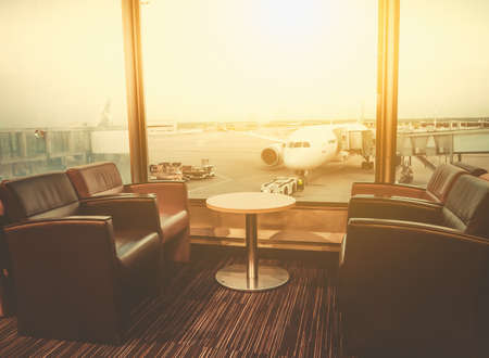 Foto de Departure lounge at the airport with seating and table with aircraft preparing for flight in the background - Imagen libre de derechos