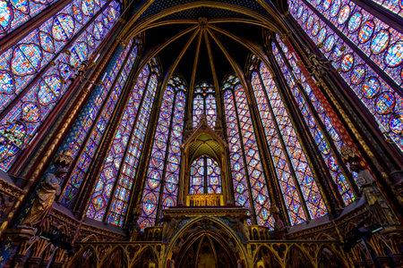 Foto de PARIS, FRANCE - MAY 22: Stained Glass Interior in The Sainte-Chapelle in Paris, France. The Sainte-Chapelle is a royal chapel in the Gothic style, within the medieval Palais de la Cite - Imagen libre de derechos