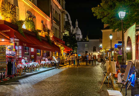 Foto de Typical night view of cozy street with tables of cafe and easels of street painters in quarter Montmartre in Paris, France - Imagen libre de derechos