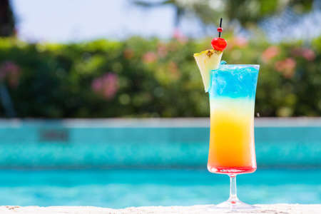 Photo for Glass of Rainbow cocktail on the pool nosing at the tropical resort. Horizontal, cocktail on right side - Royalty Free Image