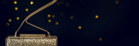 Photo pour Festive evening golden clutch with star sprinkles on black. Holiday and celebration background. Luxury accessories and party concept. Christmas and New Year Celebration. Horizontal - image libre de droit