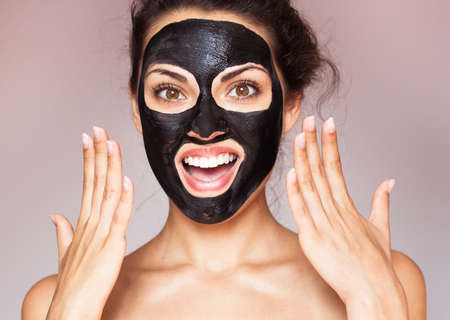 Photo pour Young beautiful woman in a mask for the face of the therapeutic black mud. Spa treatment - image libre de droit
