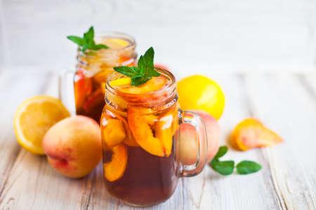 Foto de Homemade iced lemonade with ripe peaches and fresh mint. Fresh peach ice tea in a mason jar. Copy space background. - Imagen libre de derechos