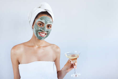 Foto de Young beautiful woman in face mask of therapeutic blue mud. - Imagen libre de derechos