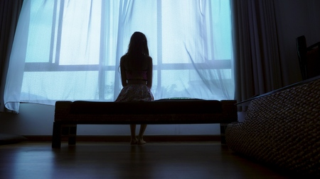 Foto de little teenager looking out of the window in bad weather, silhouette of a fragile teenager girl on the background of a large window - Imagen libre de derechos