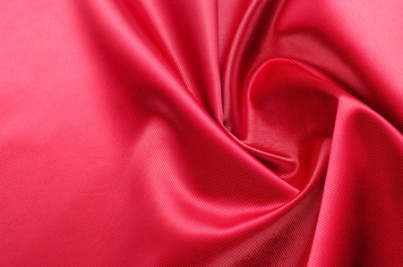 Photo pour Texture, background, pattern. Red silk fabric.This satin fabric is perfect for making fabric flowers for use in hair accessories, jewery making, and fabric bouquets.  - image libre de droit