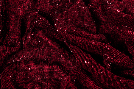 Photo for Texture, background, pattern, red fabric with paillettes. Look at these neon red sequins. Round neon pink sparkles glitter overlapping iridescent glitter on a clean purple grid. - Royalty Free Image
