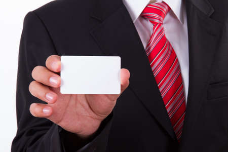Businessman in dark suit and white shirt with red striped tie, shows white blank business card with space.