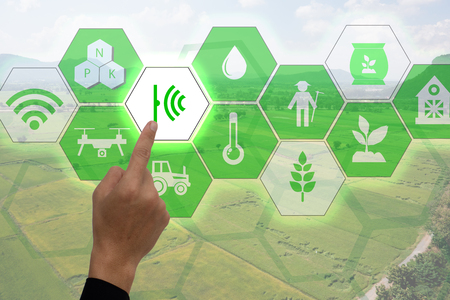 Foto de Internet of things(agriculture concept),smart farming,industrial agriculture.Farmer point hand to use augmented reality technology to control ,monitor and mangement in the field - Imagen libre de derechos