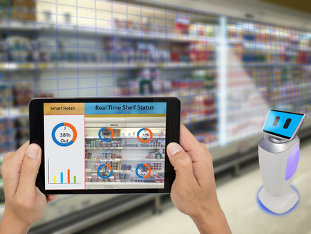 Foto de smart retail concept, A store's manager can check what data of real time insights into shelf status which report on a tablet from artificial intelligence(ai) smart robot while scanning goods and price - Imagen libre de derechos